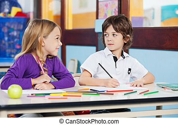 Boy Looking At Female Friend While Drawing In Classroom