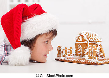Boy looking at gingerbread house