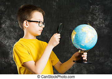 Boy looking at globe with magnifying glass