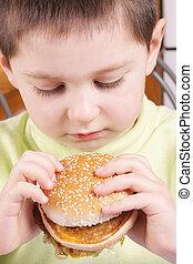 Boy looking at hamburger