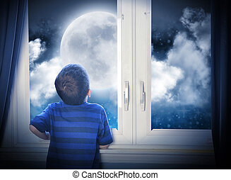 Boy Looking at Night Moon and Stars - A young boy is looking...