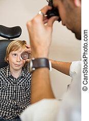 Boy Looking At Optician Examining His Eyes Through Lens