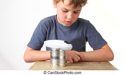 boy looking at rotating automatic opener for cans