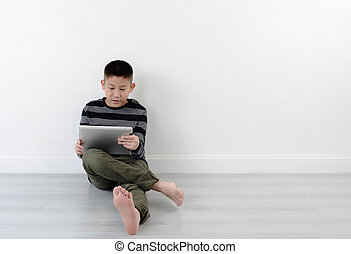Boy looking at touch pad at home