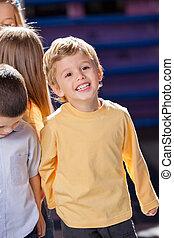 Boy Looking Away With Friends In Kindergarten - Happy little...