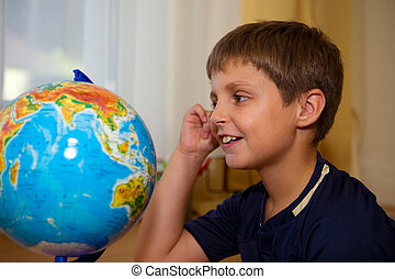 boy looking globe of world