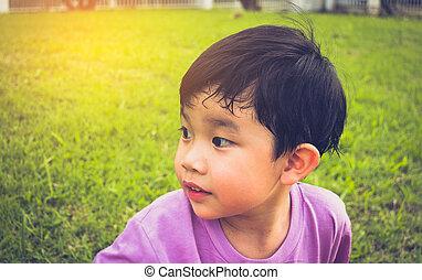 boy looking on left side in park.