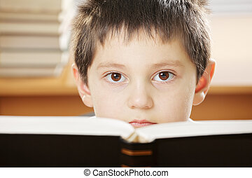 Boy looking over book