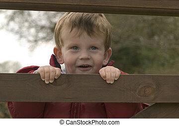 Boy looking through bars of gate