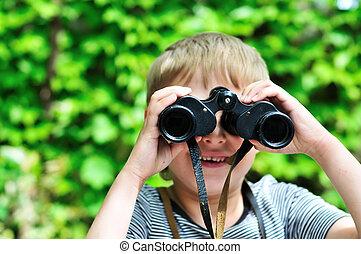 Boy looking through binocular in selective focus