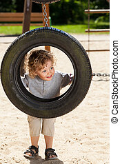 Boy looking through tire swing
