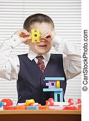 Boy looking through toy block