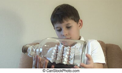 boy looks at a model of the ship