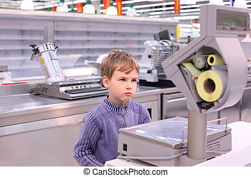 boy looks at scales in empty shop - boy looks at scales in...