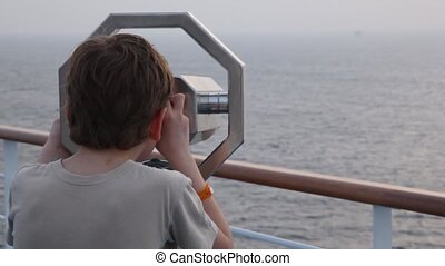 boy looks at sea through binocular on deck of cruiser