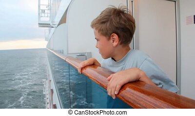 boy looks at water, leaning on handrail of board of ship