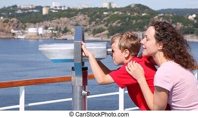 Boy looks in binocular on ship deck under direction of mother