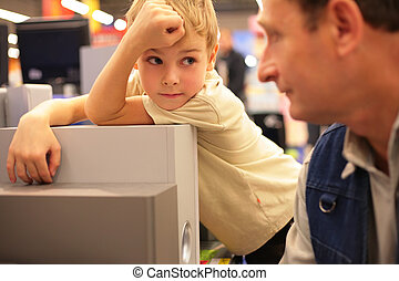 Boy looks on grandfather in shop