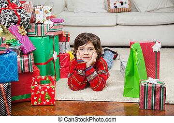 Boy Lying Besides Stacked Christmas Gifts