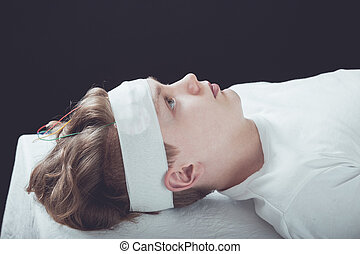 Boy Lying Down with Bandage Wrapped Around Head