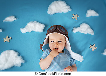 boy lying on blanket with white clouds