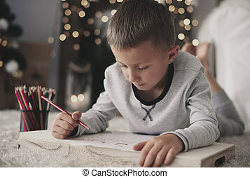 Boy lying on front and drawing