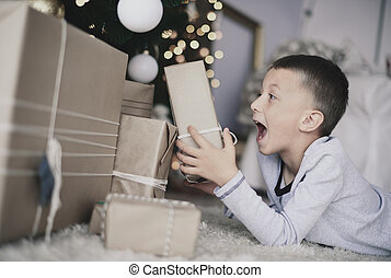 Boy lying on front and watching gifts
