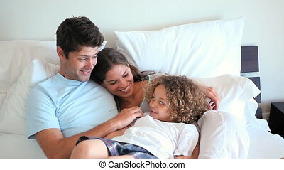 Boy lying on his parents