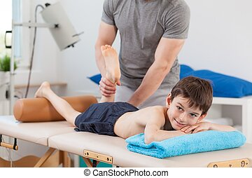 Boy lying on physiotherapy table and having a leg massage