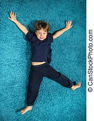Boy lying on the carpet