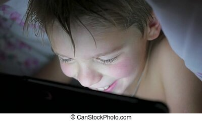 boy lying under blanket and watching cartoons on touch pad -...