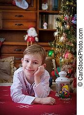 Boy lying under Christmas tree