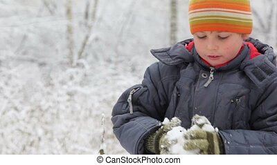 boy makes and throws snowball in winter forest