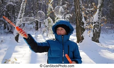 boy makes big soap bubbles in the Park with delight on a Sunny day