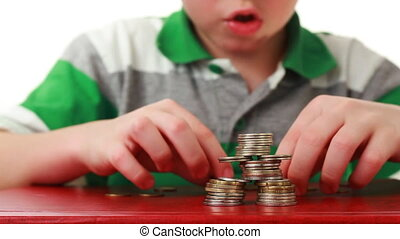 boy makes complicated figure with coins on red base