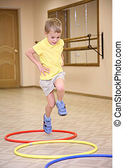 boy makes exercise with hoops