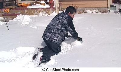 Boy making large snowball