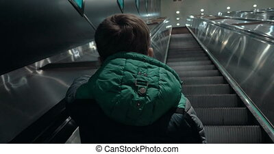 Boy moving up on escalator in subway