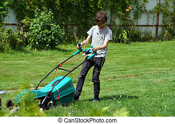 Boy mowing the lawn with lawnmower