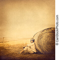 Boy next to haystack, vintage effect