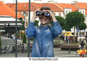 Boy observing city using binoculars.