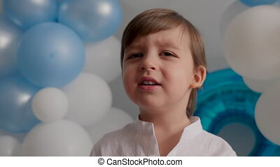 boy of two years in a white shirt sitting at home in blue balloons