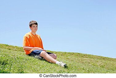 a young boy in an orange shirt sitting on a grassy hill with a blue sky behind