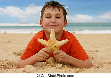 Child on sandy beach holds a starfish - focus on boy only. 1/500 @ f5