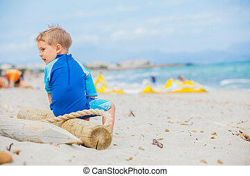 Back view cute 2 years old boy looking at kiting on tropical beach