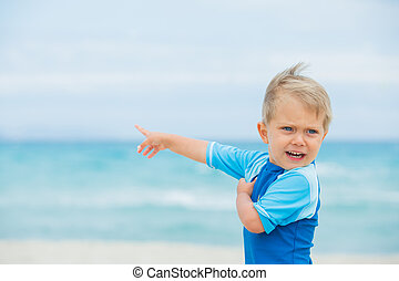 Back view cute 2 years old boy runing on tropical beach