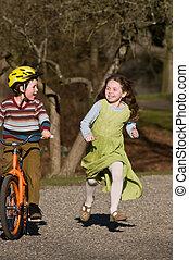 boy on bike, girl running beside him