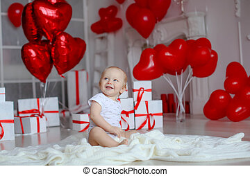 Boy on birthday party 1 year on the background of red balloons