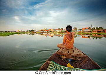 Boy on boat - Cambodian boy on prow of small boat...