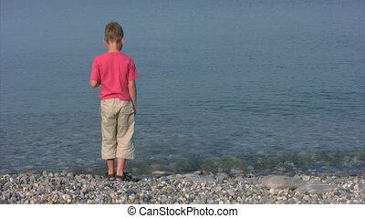 boy on coast throws stones into sea